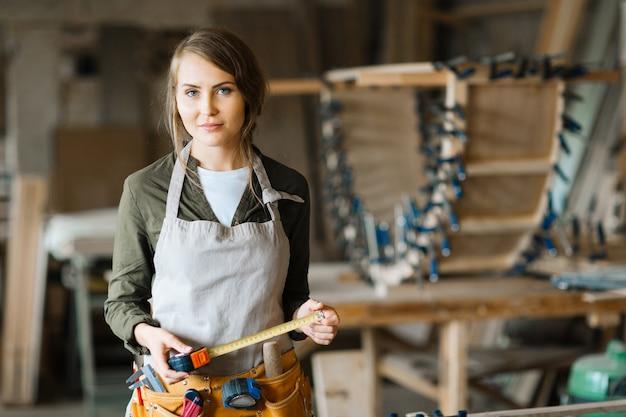 Blonde houtbewerker met meetlint