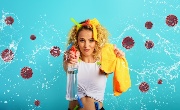Blonde huisvrouw spettert desinfectiemiddel om virussen en bacteriën van covid-19 te verwijderen. cyaan achtergrond