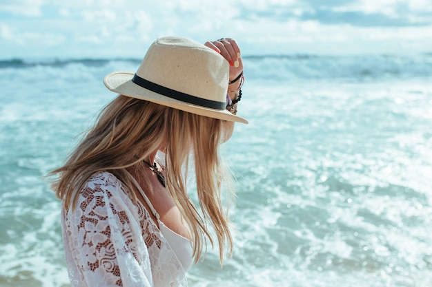 Blonde in een hoed bij de zee