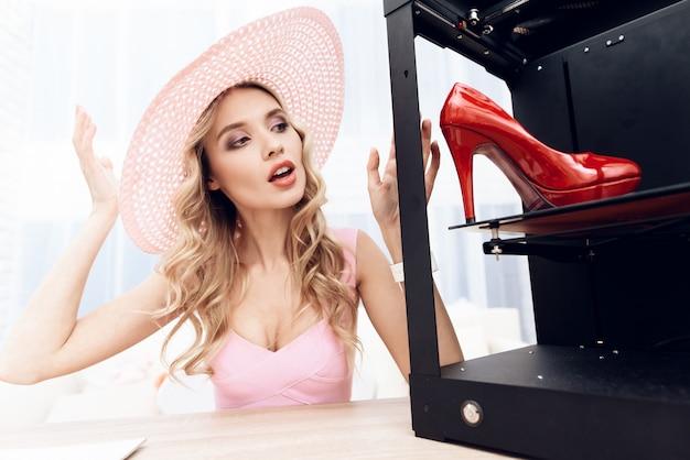 Blonde in een roze jurk kijkt naar een rode schoen in een 3d-printer.