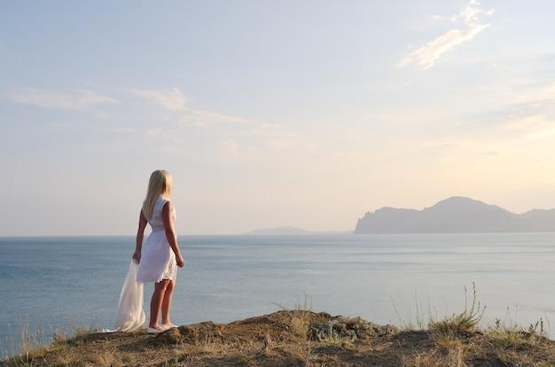 Blonde in een witte jurk staat op de berg en kijkt naar de zee