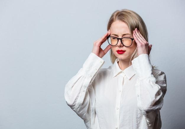 Blonde in glazen en wit overhemd met hoofdpijn op witte muur