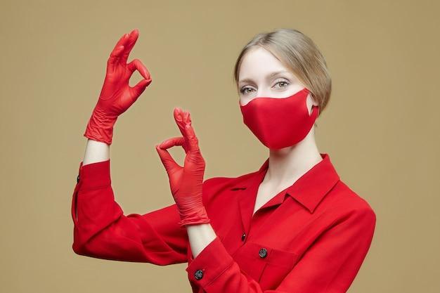 Blonde in rode handschoenen en een masker toont het ok-teken. het concept van het voorkomen van coronavirus covid 19.
