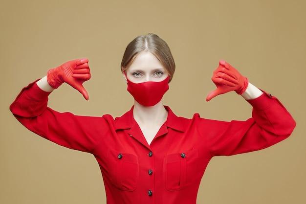 Blonde in rode handschoenen en een masker wijst haar duim naar beneden. het concept van het voorkomen van coronavirus covid 19.