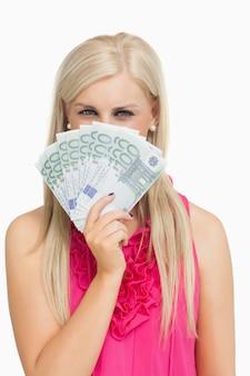 Blonde in roze die 100 euro bankbiljetten houdt