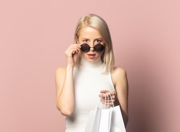 Blonde in top met boodschappentassen op roze
