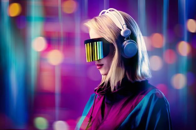 Blonde in vr-bril en koptelefoon op roze ruimte