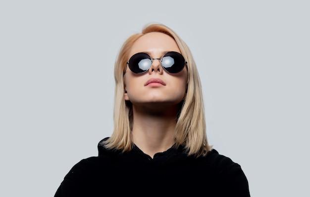 Blonde in zwarte en ronde zonnebril op een witte achtergrond