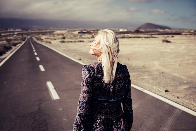 Blonde jonge dame vrouwelijke wandeling op een lange weg in de woestijn