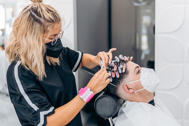 Blonde jonge kapper krult het haar van een man met rollers tijdens het gebruik van een masker