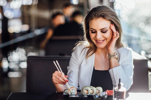 Blonde, jonge mooie blonde meisjeszakenvrouw die sushi eet op het zomerterras in een japans restaurant.