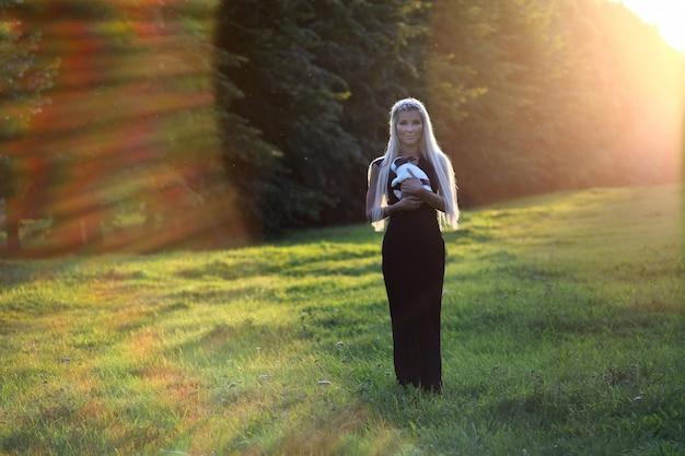 Blonde jonge vrouw bruid glimlachend en schattig konijn te houden. zomer buitenpark locatie. mensen en huisdieren concept. mooie jonge vrouw met haar konijntje