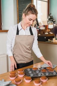 Blonde jonge vrouw die de muffins verwijdert uit het bakseldienblad