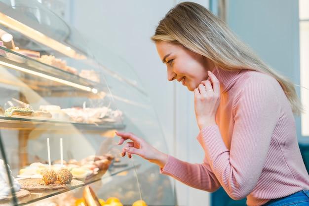Blonde jonge vrouw die door het kabinet van de cakeweergave in koffie kijkt