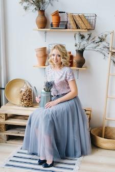 Blonde jonge vrouw die een bloem en een metaalgieter in een het planten balkonbinnenland houden. gezonde levensstijl. nul afval thuis concept.