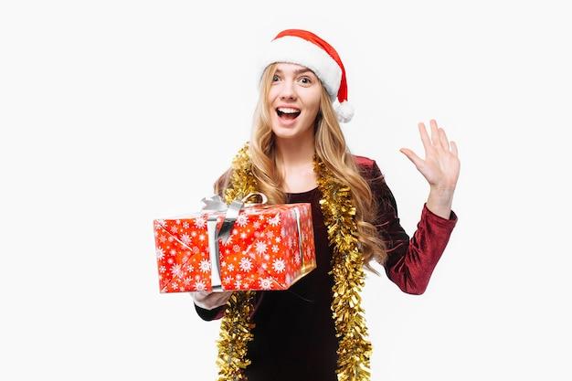 Blonde jonge vrouw die een kerstmuts draagt