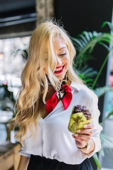 Blonde jonge vrouw die gebakken chocolademuffin in de hand bekijkt
