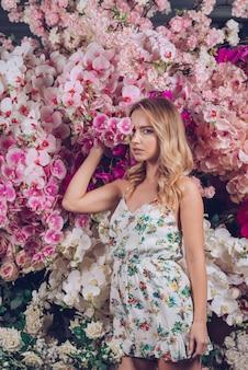 Blonde jonge vrouw die haar één ogen behandelen met roze orchidee