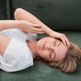 Blonde jonge vrouw die haar ogen rust