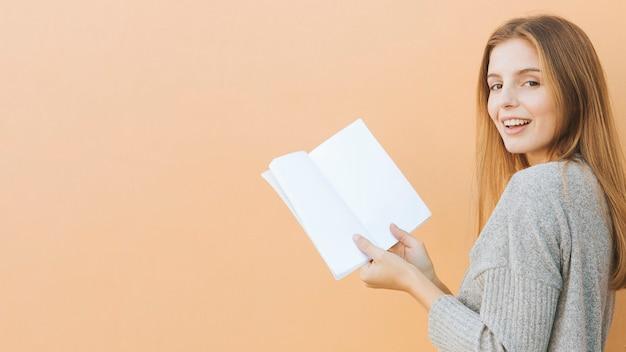 Blonde jonge vrouw die het boek van de cameraholding in hand tegen perzikachtergrond bekijken