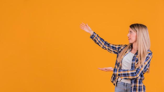 Blonde jonge vrouw die iets voorstellen tegen een oranje achtergrond