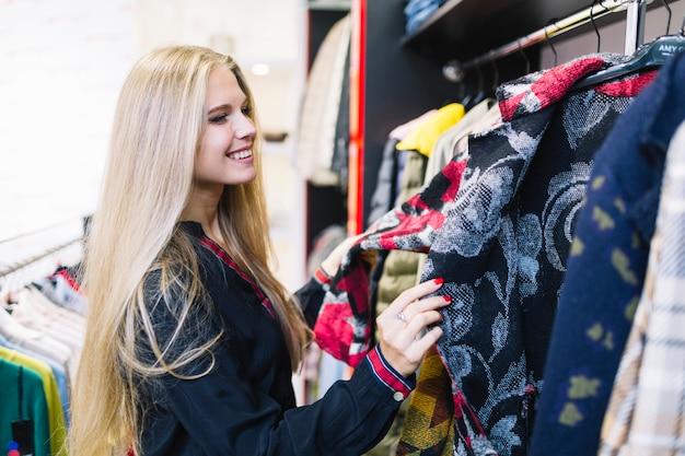Blonde jonge vrouw die jasjes in het rek bekijkt