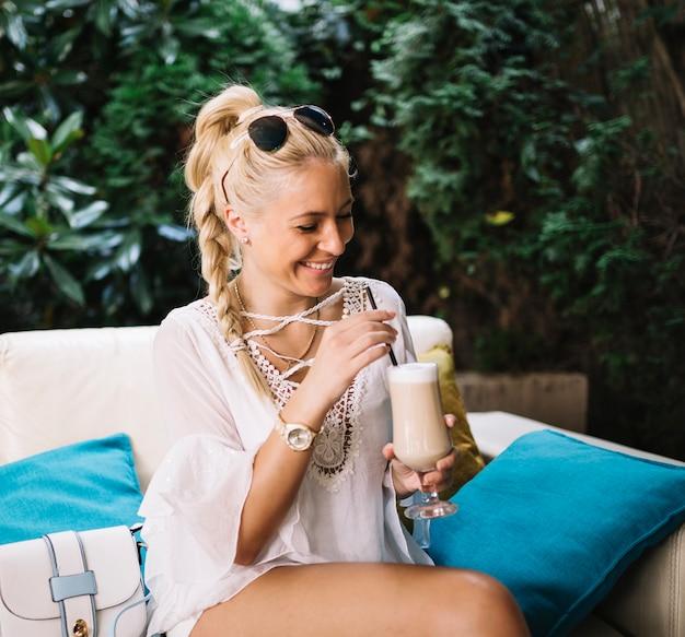 Blonde jonge vrouw die latte macchiato in het glas roert
