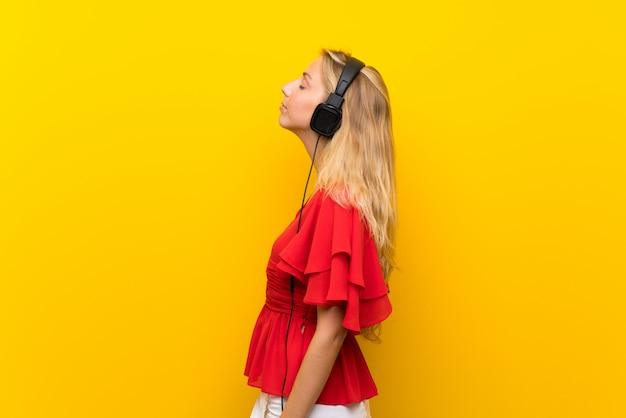Blonde jonge vrouw die over gele muur aan muziek met hoofdtelefoons luistert