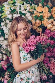 Blonde jonge vrouw die roze in hand de status van rozen voor bloemachtergrond houdt