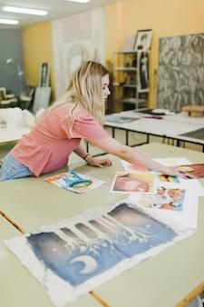 Blonde jonge vrouw die schilderijen op werkbank bekijken