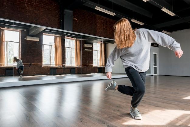 Blonde jonge vrouw die tegen de spiegel in de dansstudio dansen