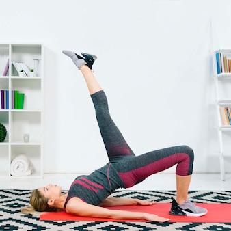Blonde jonge vrouw die thuis het ontspannen oefening doet