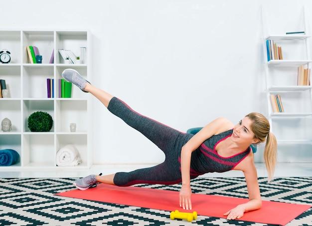 Blonde jonge vrouw die uitrekkende oefening op tapijt in de woonkamer doet