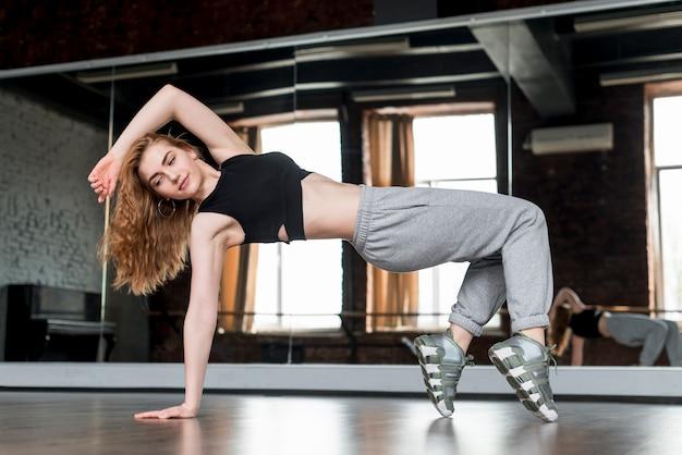 Blonde jonge vrouw die voor spiegel dansen