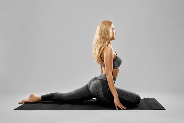 Blonde jonge vrouw die yogaoefeningen doet met een goed humeur