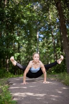 Blonde jonge vrouw doet firefly yoga houding