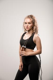 Blonde jonge vrouw in activewear springtouw op haar schouder met pauze na de training