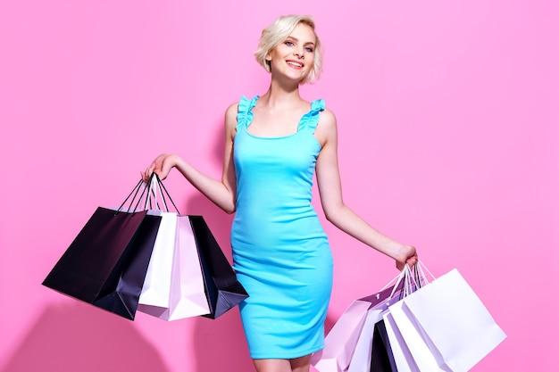 Blonde jonge vrouw in een blauwe jurk houdt boodschappentassen op een roze achtergrond