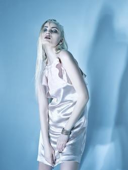 Blonde jonge vrouw in elegante jurk.