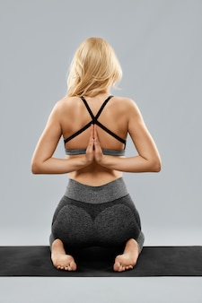 Blonde jonge vrouw in pose yoga in trendy sportkleding