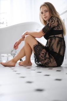 Blonde jonge vrouw in sexy lingerie in de badkamer