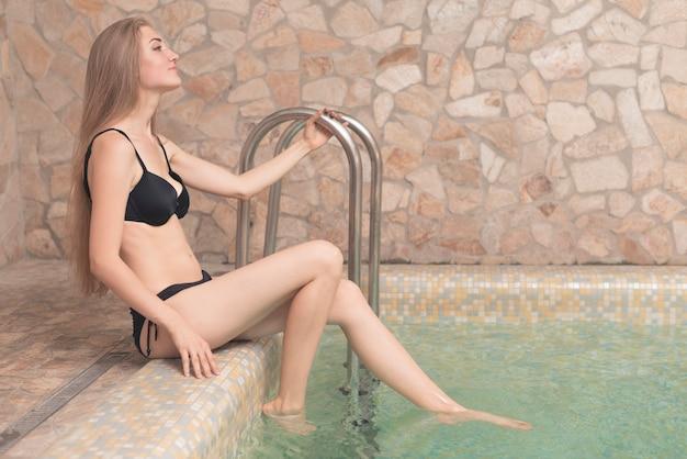 Blonde jonge vrouw in zwarte bikini zittend op de rand van het zwembad