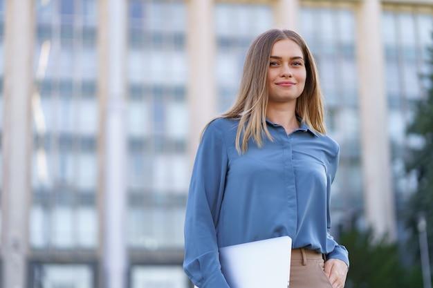 Blonde jonge vrouw lachend portret blauw zacht shirt dragen over de bouw