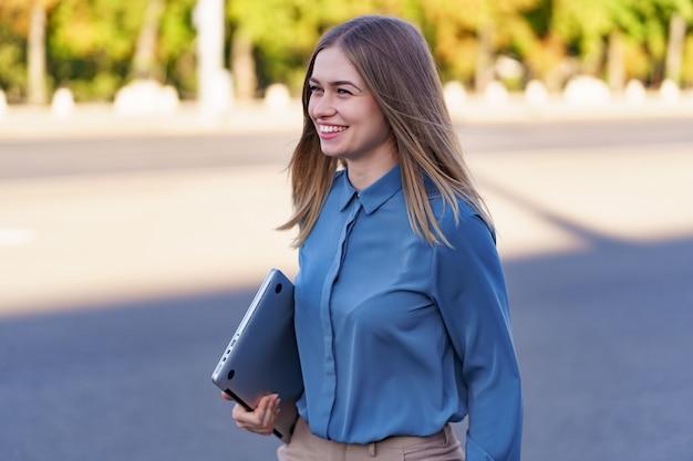 Blonde jonge vrouw lachend portret blauw zacht shirt dragen