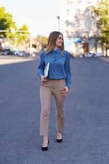 Blonde jonge vrouw lachend portret draagt blauw zacht shirt met een laptop tijdens het lopen