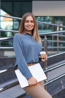 Blonde jonge vrouw lachend portret met laptop en koffie, blauwe zachte shirt dragen over modern gebouw achtergrond