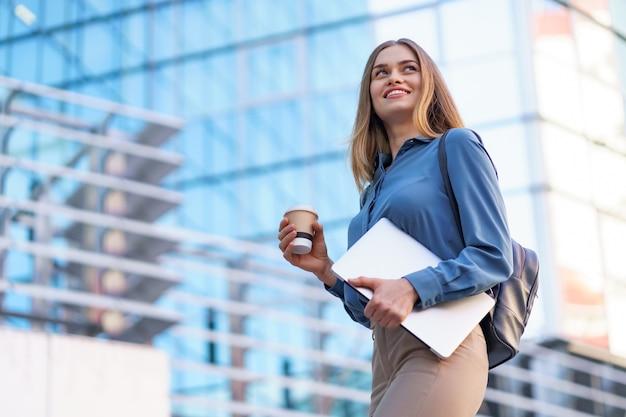 Blonde jonge vrouw lachend portret met laptop en koffie, blauwe zachte shirt dragen over modern gebouw