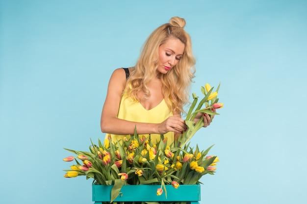 Blonde jonge vrouw met bos tulpen op blauwe achtergrond.
