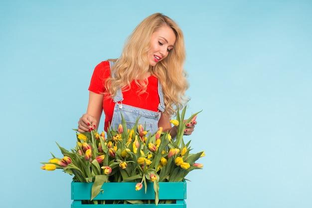 Blonde jonge vrouw met bos tulpen op blauwe muur
