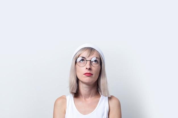 Blonde jonge vrouw met een bril, een witte hoed kijkt op tegen een lichte achtergrond.